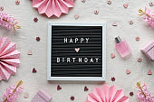Text Happy Birthday on letter board, letterboard. Creative flat lay, top view on cream white textile. Party decor, paper fans, gift boxes. Natural pink hyacinth flowers, glass bottle with perfume