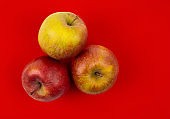 Fresh red apple on red background