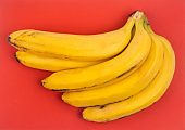 bunch of bananas on red background