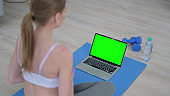 Rear View of Young Woman doing Yoga while Looking at Laptop with Chroma Key Screen