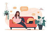 Woman sitting on couch and working on laptop, freelance and learning at home