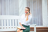 Young beautiful happy woman businesswoman with notepad and phone