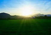 Rays of light falling on the green fields above misty mountains