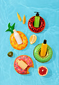 Summer vacation cosmetics. Sun protection lotion, sunscreen, moisturizer. Summer skin care concept. Mockup of sunscreen products in bottles on bright background with fruits