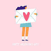 Happy young woman holding a big envelope with a love letter. Greeting card for Valentine's Day.