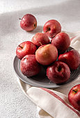 Red apples close up on grey plate. Still life in rustic style