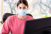 Businesswoman wearing face mask while working on computer