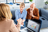 Couple getting advice from businesswoman while sitting at home in the living room