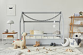 Stylish scandinavian child's room with creative wooden bed, wooden cube, lamp, wooden shelf, plush and wooden toys and hanging textile decorations. Grey walls, carpet on the floor. Template.