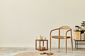 Neutral concept of living room interior with design wooden chair, round carpet, cup of coffee, tray, stool, slippers, decoration and elegant personal accessories. Template. Copy space.