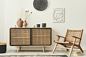 Stylish scandinavian living room interior of modern apartment with wooden commode, design armchair, carpet, dried flowers and personal accessories in unique home decor. Template.