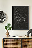 Minimalist composition of living room interior with black mock up poster map, wooden commode, black round decoration, leaf in vases and elegant personal accessories. Template.