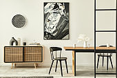 Stylish scandinavian living room interior of modern apartment with wooden commode, design table, chairs, carpet, abstract paintings on the wall and personal accessories in unique home decor. Template.