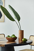 Minimalist composition on the design wooden table with fruits, tropical leaf in vase, abstract painitngs and stylish chair. Modern dining room. Template.