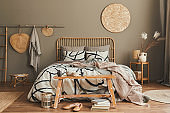 Stylish composition of bedroom interior with wooden bed, furniture, dried flowers in vase, rattan decoration, vases and elegant accessories. Beautiful bed sheets, blanket and pillows. Cozy home decor.