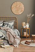 Wooden bed in stylish neutral bedroom interior with design furniture, decoration, carpet, book, dried flowers in vase, bed sheets, blanket, pillows and elegant personal accessories in home decor.