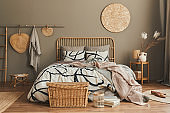 Stylish composition of bedroom interior with wooden bed, furniture, dried flowers in vase, rattan decoration and elegant accessories. Beautiful bed sheets, blanket and pillows. Cozy home decor.