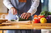 a female chef cutting and chopping vegetables by knife on wooden board in kitchen