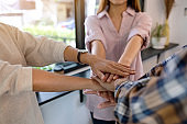 business team standing and joining their hands together in office