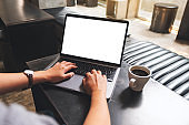 a woman using and typing on laptop computer with blank white desktop screen in cafe