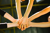 Unite Hands, teamwork concept. Sports people joining hands. Female team ready to successful match.