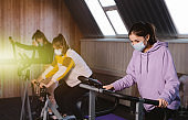 Group of young beautiful female athletes wearing face masks doing warm-up aerobics in the gym. Fitness training workout on treadmills. Infection prevention and control of epidemic