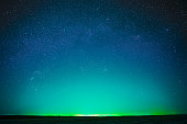 Beautiful Night Sky Glowing Stars Background Backdrop With Colorful Sky Gradient. Colourful Night Starry Sky In Blue Aquamarine Green Colors. Dark Ground. Copy Space