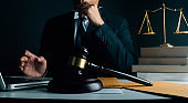 Business and lawyers discussing contract papers with brass scale on desk in office. Law, legal services, advice, justice and law concept picture with film grain effect