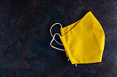 Face protective mask. Reusable antivirus mask made from yellow cotton. Yellow protective mask on a dark background. Eco-friendly tailoring. Top view. Copy space