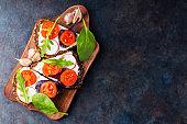 Bruschetta with cream cheese, cherry tomatoes and garlic on a cutting board. Italian antipasti bruschetta with cream cheese and fresh herbs. Copy space. Top view