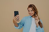 Pretty young woman makes selfie with smart phone