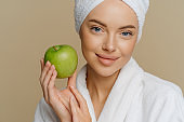 Close up shot of blue eyed woman with minimal makeup well cared complexion fresh clean skin dressed in white coat holds green apple isolated over brown background. Natural cosmetics concept.