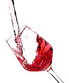 Red wine is pouring into a glass goblet on a white background.