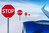 Flight ban and closed borders for tourists and travelers. No-fly zone concept. Airplane in flight with a STOP sign