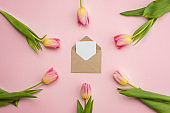 An envelope with a postcard is arranged in the center on a pink background and pink tulips are laid out in a circle. Spring concept, mother's day, women's day