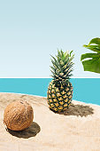 A natural coconut, organic pineapple and monstera leaf on sandy beach, concept for summer vacation.