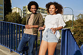 Couple standing leaning against the railing and talking together