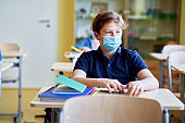 Student in protective mask in the classroom looking away