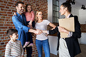 Family shaking hands with real estate agent in new apartments
