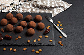 Homemade vegan truffles with dried fruits, walnuts and raw cocoa powder served on black slate plate.