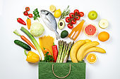 Healthy food background. Healthy food in paper bag fish, vegetables and fruits on white. Shopping food supermarket concept. Healthy eating, planning meal, food buying