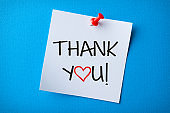White Sticky Note With Thank You And Red Push Pin On Blue Background