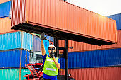 Foreman is giving a signal to work in the harbor. To move the cargo container onto the ship. Foreman signal contianer.