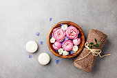 Beauty, aromatherapy and spa background with perfumed water with flowers in wooden bowl, towel and candles on stone table. Top view, flat lay.