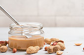 Peanut butter in a glass jar, peanuts, kitchen knife on white background. Vegan food. Close up