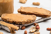 Peanut butter in a glass jar, peanuts, kitchen knife and peanut butter sandwiches on white background. Vegan food