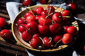 Fresh cherry fruit in plate on wooden background