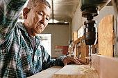 Carpenter using drilling machine
