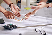Designer and client discussing blueprint