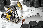Oil pump jack and barrels on newpaper with growth of price of crude oil. Stock market of crude oil, investment and petroleum industry.